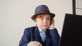 小男孩叫由手机前面膝上型计算机在营业所 年轻商人谈话在智能手机一会儿之前 股票录像
