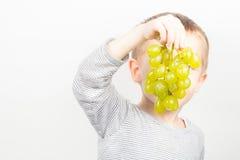 男孩用葡萄 库存照片