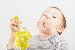男孩用葡萄 免版税图库摄影