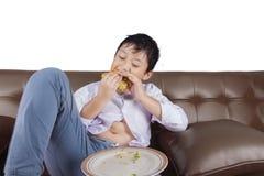 小男孩吃在长沙发的乳酪汉堡 图库摄影