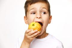 小男孩吃着苹果演播室射击 免版税图库摄影