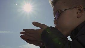 小男孩吹从他的手的雪花反对与太阳的蓝天 股票录像