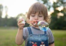小男孩吹的肥皂泡 免版税库存照片