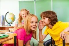 小男孩告诉秘密给其他女孩在学校 免版税库存照片
