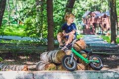 小男孩和他的自行车 在自行车的学龄前儿童` s第一天 运动喜悦  免版税库存照片
