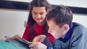 小男孩和女孩在说谎在床上的片剂的使用和狗 男孩和女孩青少年社会媒介互联网 股票录像