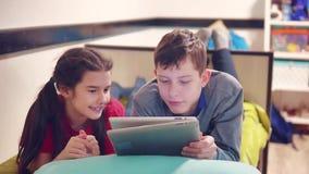 小男孩和女孩在说谎在床上的片剂的使用和狗 a的男孩和女孩青少年社会媒介互联网 股票录像