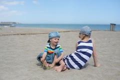 小男孩和女孩坐海滩 免版税库存图片
