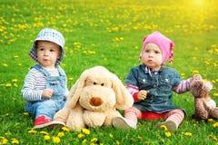 小男孩和女孩帽子的坐领域与软的玩具在夏天 免版税库存照片