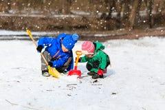 小男孩和女孩开掘的雪在冬天 免版税图库摄影