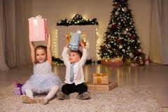 小男孩和女孩开放圣诞礼物新年冬天圣诞树 免版税图库摄影