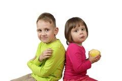 小男孩和女孩用苹果在紧接坐的手上 库存图片
