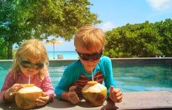 小男孩和女孩饮用的椰子鸡尾酒在海滩胜地 免版税库存照片