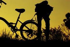 小男孩和女孩骑马骑自行车在日落,活跃孩子炫耀,亚洲孩子,现出轮廓孩子在日落,愉快的时间 库存图片