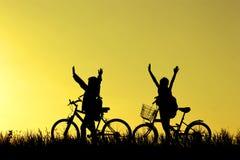 小男孩和女孩骑马骑自行车在日落,活跃孩子炫耀,亚洲孩子,现出轮廓孩子在日落,愉快的时间 库存照片