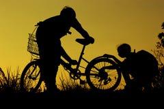 小男孩和女孩骑马骑自行车在日落,活跃孩子炫耀,亚洲孩子,现出轮廓孩子在日落,愉快的时间 免版税库存照片