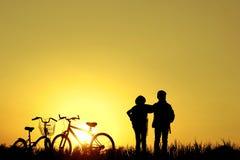 小男孩和女孩骑马骑自行车在日落,活跃孩子炫耀, A 库存图片