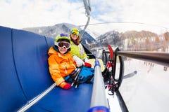 小男孩和母亲滑雪电缆车椅子的 库存图片