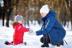 小男孩和获得中年的妇女与雪的乐趣 户外激活与孩子的家庭休闲在冬天 免版税库存照片