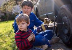 小男孩和他的父亲变速轮在汽车 库存图片