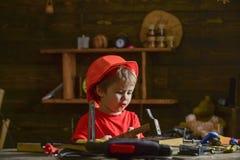 小男孩唱歌歌曲,当锤击钉子入木块时 坐在工作表上的小孩子在车间 库存照片