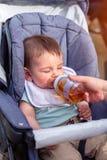 小男孩喝从瓶的汁液,当坐在婴儿车时 图库摄影