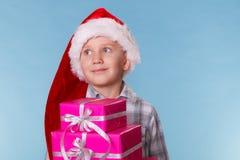 小男孩圣诞老人有桃红色礼物盒的帮手帽子 库存图片