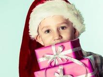 小男孩圣诞老人有桃红色礼物盒的帮手帽子 免版税库存图片