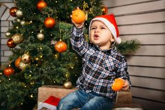 小男孩圣诞节画象红色圣诞老人帽子的坐有礼物的箱子用桔子在手上在圣诞树附近 库存照片
