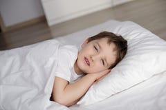 小男孩在与开放的眼睛的白色床上在 免版税库存图片