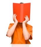 小男孩在书后掩藏 免版税库存照片