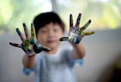 小男孩在五颜六色的油漆背景中绘了手:在外面 图库摄影