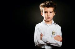 小男孩在低调的商人画象与横渡的胳膊 免版税库存照片