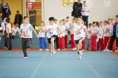 小男孩在体育场内跑在儿童竞争 免版税库存照片