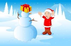 小男孩在使用与雪人的圣诞老人穿戴了有冬天背景 库存照片