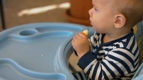 小男孩在儿童` s椅子坐并且吃小圆面包片断  免版税图库摄影