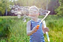 小男孩在公园做泡影肥皂外面 免版税库存照片