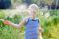 小男孩在公园做泡影肥皂外面 库存照片