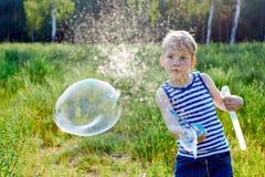 小男孩在公园做泡影肥皂外面 免版税库存图片