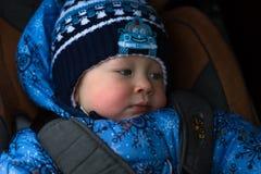 小男孩在冬天在儿童汽车座椅穿衣 免版税库存照片