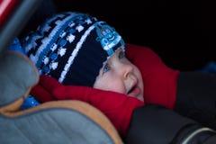 小男孩在冬天在儿童汽车座椅穿衣 库存图片