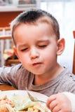 小男孩在厨房用桌上 免版税库存图片