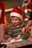 小男孩在圣诞节烘烤的圣诞老人帽子 库存照片
