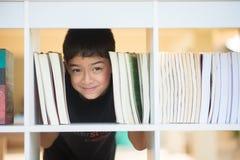 小男孩在学校面孔的图书馆里在书之间 图库摄影