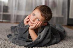 小男孩在家地毯的 免版税库存图片