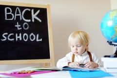 小男孩在工作场所的阅读书在学校 库存照片