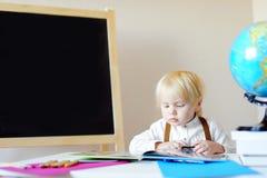 小男孩在工作场所的阅读书在学校 免版税库存图片