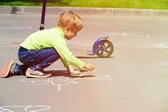 小男孩在户外沥青的图画飞机 免版税库存图片