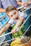 小男孩在推车坐用西瓜 免版税库存图片