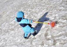 小男孩在操场使用与玩具的冬天 免版税库存照片